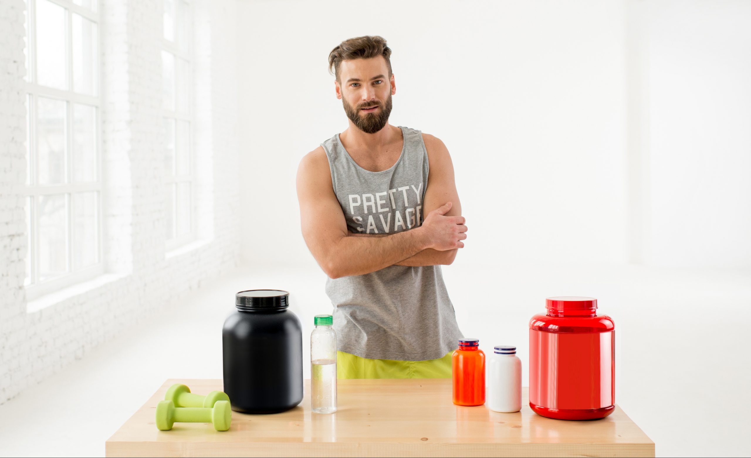 Portrait of athletic man in sportswear with proteins and vitamins in the white gym interior
